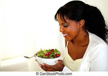 Black woman smiling and looking to a green salad