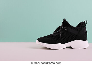 Black woman sneakers on a gray table