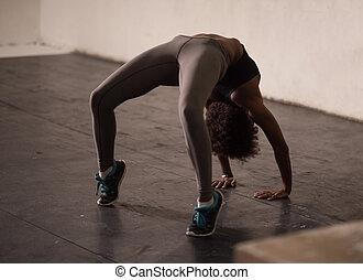 black woman standing in bridge pose