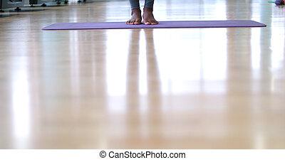 black woman standing on yoga mat