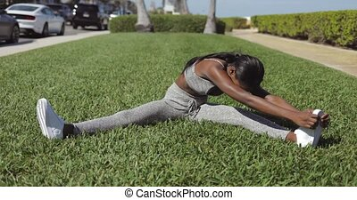 Black woman stretching in sunny park
