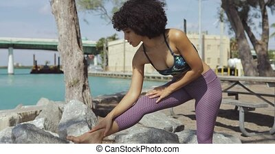 Black woman stretching on riverbank