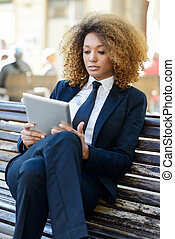 Black woman using tablet computer in town