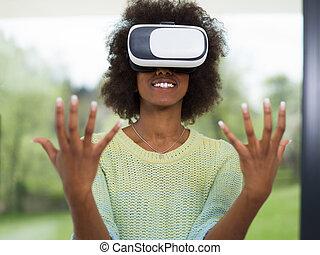 black woman using VR headset glasses of virtual reality -...