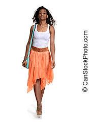 black woman walking wearing orange