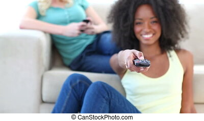 Black woman watching TV while a friend is on a couch using...