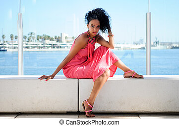 Black woman with pink dress and earrings. Afro hairstyle