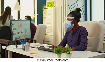Black woman with protection face masks working on computer in workplace during pandemic. Multiethnic team in new normal business financial office checking reports, analysing datas looking at desktop