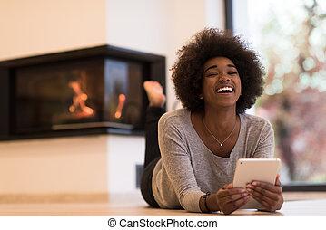 black women using tablet computer on the floor