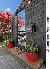 Black wood house with door and red flower pots.