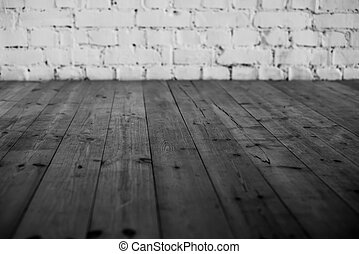 Black wooden floor and white brick wall background