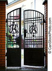 Black wrought iron and brick entrance gates