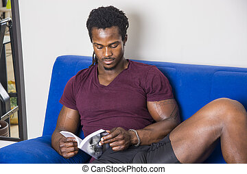Black young man at home reading a book