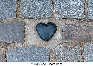 Black zen heart shaped rock on a tile background