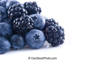Blackberries and blueberries in a pile - Close up of ...
