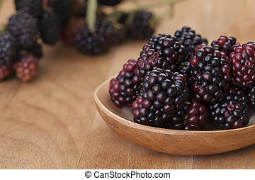 Blackberries in a spoon on wooden background