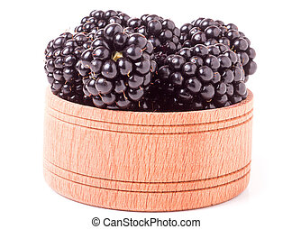 Blackberries in a wooden bowl isolated on white background