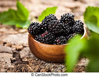 Blackberry  - Blackberries in bowl on wooden background.