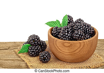 blackberry in bowl on wooden table isolated on a white background. Clipping path and full depth of field