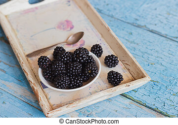 Blackberry in the white bowl on the wooden tray