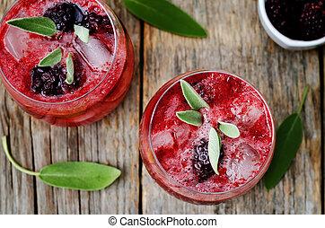 blackberry sage cooler on a dark wood background. the...