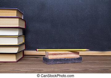 blackboard, eraser and books on desk