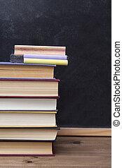 blackboard, eraser, chalk and books on desk