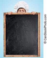 Blackboard for menu. - Restaurant chef hiding behind a big...