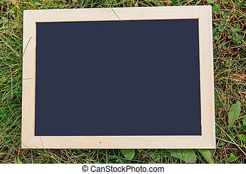 Blackboard on green grass