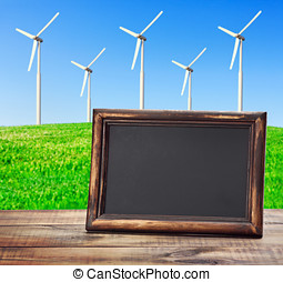 blackboard on the table against the background of wind power