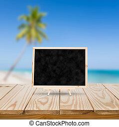 Blackboard on wood table and blue sea background