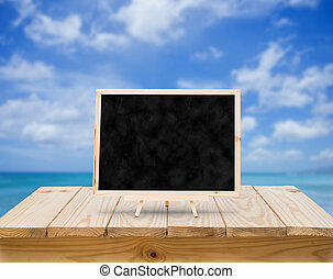 Blackboard on wood table with blue sky background
