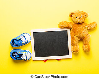 photo of empty blackboard, cute teddy bear and little child gumshoes on the wonderful yellow studio background