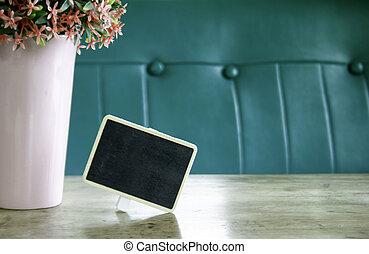 blackboard with flower in vase