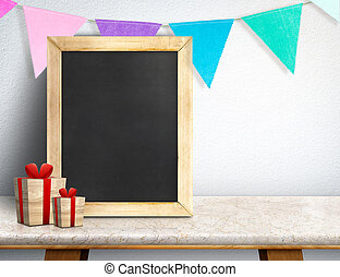 Blackboard with gift box and colorful flag banner on marble table at white wall, Leave space for display or montage of your design, Holiday new year concept.