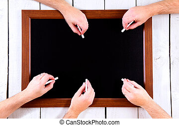 Blackboard with many hands