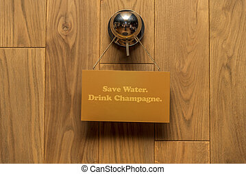 """Blackboard with text """"Save water. Drink champagne"""" on wooden background."""