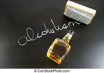 Blackboard with the word ALCOHOLISM written in chalk with an eraser and a mini bottle of whiskey