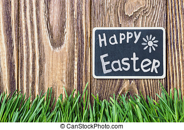 blackboard with the words Happy Easter and green grass
