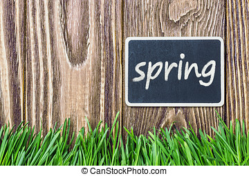 blackboard with the words spring and green grass