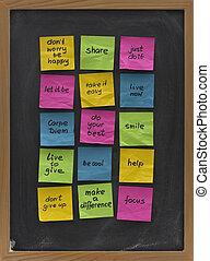 colorful crumpled sticky notes with uplifting and motivational words of wisdom posted on blackboard