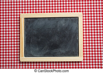 Blackboard with wooden frame on red checkered picnic tablecloth, copy space