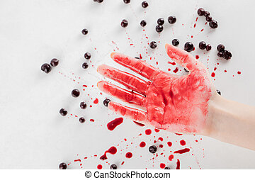 Blackcurrant confiture on white background and red syrup on the hand of a man