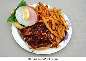 blackened fish sandwich and a french fries on a plate