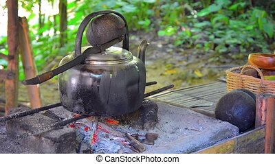 Blackened Kettle Heating over an Outdoor Cooking Fire in...