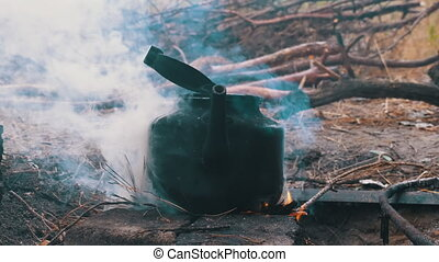 The Kettle is Boiling over an Open Fire on a Tourist Bonfire. Blackened with soot tourist kettle in the smoke on fire. Cooking at the stake. Hiking. Process preparing camping food. Summer evening.