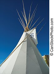 Blackfoot tepee in Calgary Alberta, with rocky mountains in the distance.