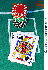 Blackjack hand with red, green and black chips.