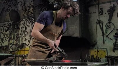 blacksmith artist in his workshop - forging a square iron to...