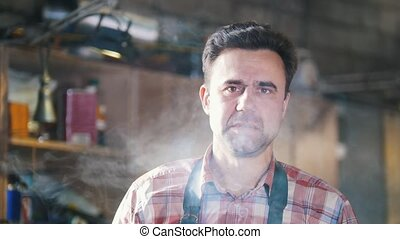 Blacksmith at work. Smoking cigarettes after work. Portrait....